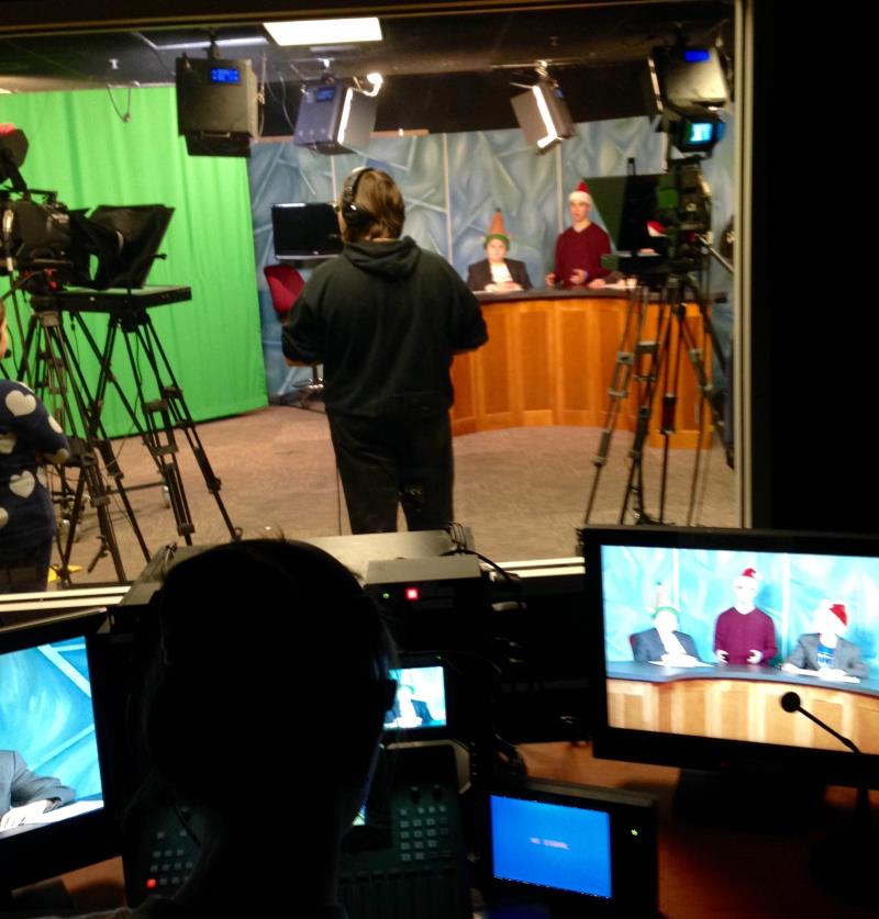 Students prepare to tape their self-produced sports news program.
